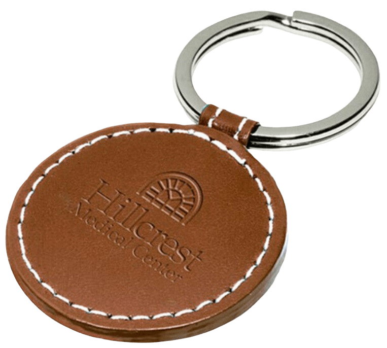 Circle shaped custom leather keyring with a stamped logo and white stiching around the edge.