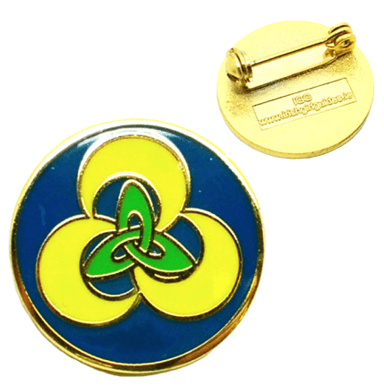 Circular custom made badge in metal. It has a distinct yellow and green logo with a protective clear coasting over the top.