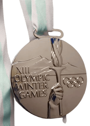 Custom made medal for the Winter Olympic Games. It has a shiny silver finish with the image of the olympic torch and rings.