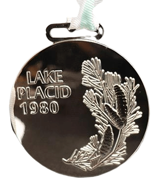 Custom made medal in silver nickel plated finish with an engraved logo.