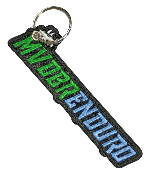 Custom embroidered keyring for a dirk bike club. It features a two colour logo and plain black fabric backing. It also has a metal split ring.