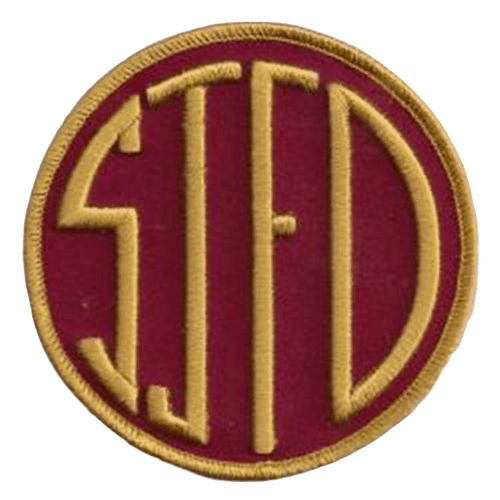 Circular embroidered patch with a stitched logo to form letters in yellow over a red fabric background.
