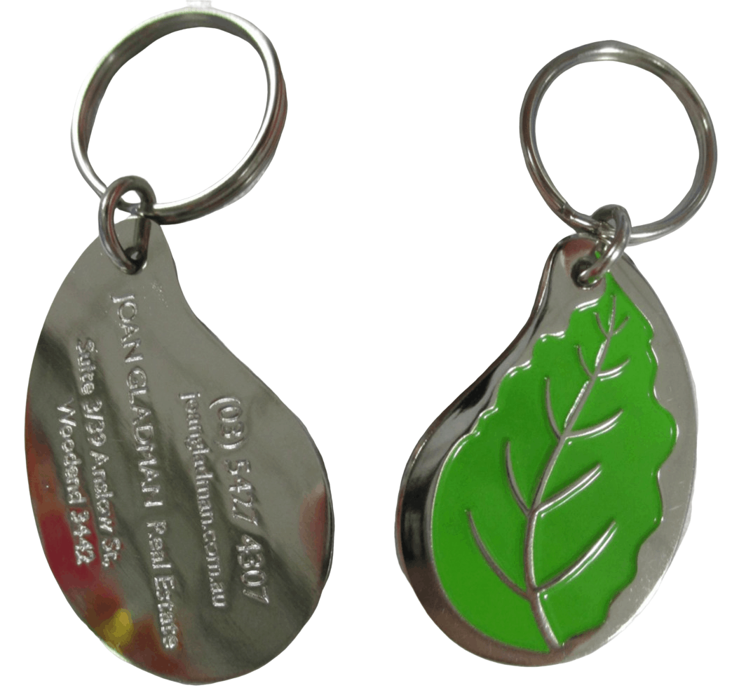 Silver custom metal key chain in the shape of a leaf for a real estate company. It features an engraved logo on both sides, and green colour print on the front.