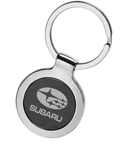 Circular custom metal keyring formed around the emblem of a popular Subaru car manufacturer.