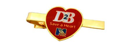 A gold plated custom tie clip with a heart shaped logo.