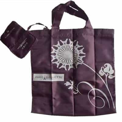 Purple coloured personalised folding shopping bag in polyester material. It has a 1 colour logo printed and folds into a neat compact pouch with a metal snap.