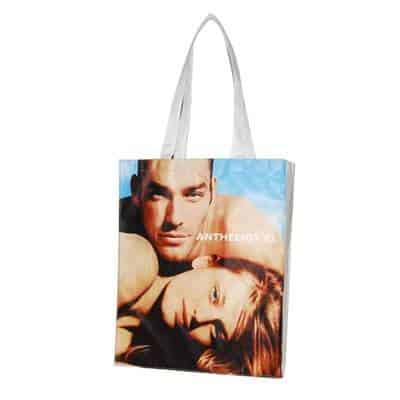 Custom non-woven shoulder bag with a man and women pictured in full colour. Material: 80G PET non-woven. Size: 36 * 45 * 8CM. Logo: heat-transfer printing process.