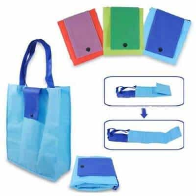 Custom non woven bag in polyester material. Various colours displayed. It neatly folds to compact pouch enclosed by a plastic buckle.