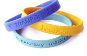 Personalised Silicone Wristband with recessed (debossed) artwork. Purple, yellow and ligh blue bands are pictured in this example.