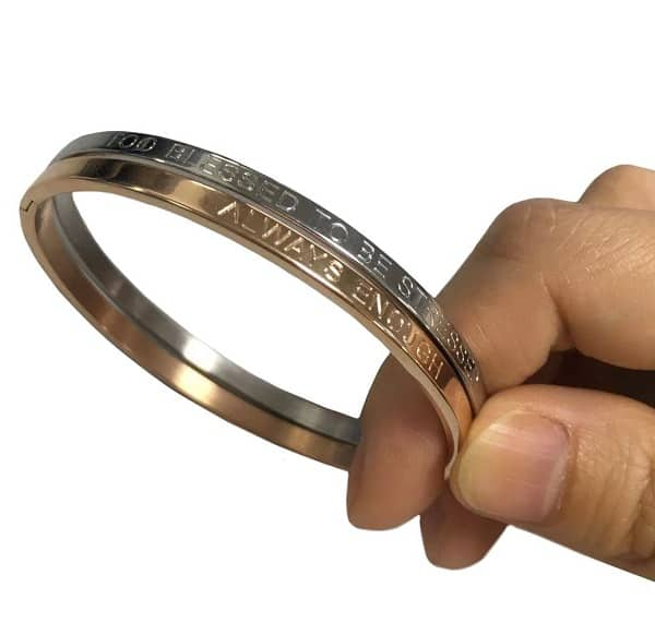 Custom metal wristband with engraved letters held by a persons fingure tips.