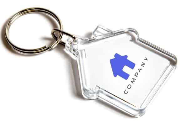 This picture shows an acrylic keyring in the shape of a house which you can brand with your own logo inside.
