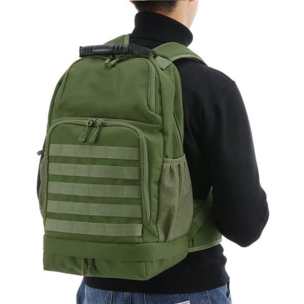 Person wearing view of a camping, hiking, military style outdoor backpack. The material is finished in army style green colour.